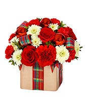 Red roses and red carnations in a square vase with a holiday ribbon