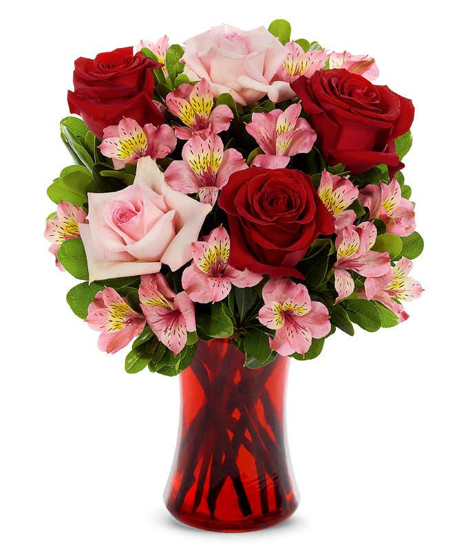 Red roses, pink roses and pink alstroemeria in a red vase
