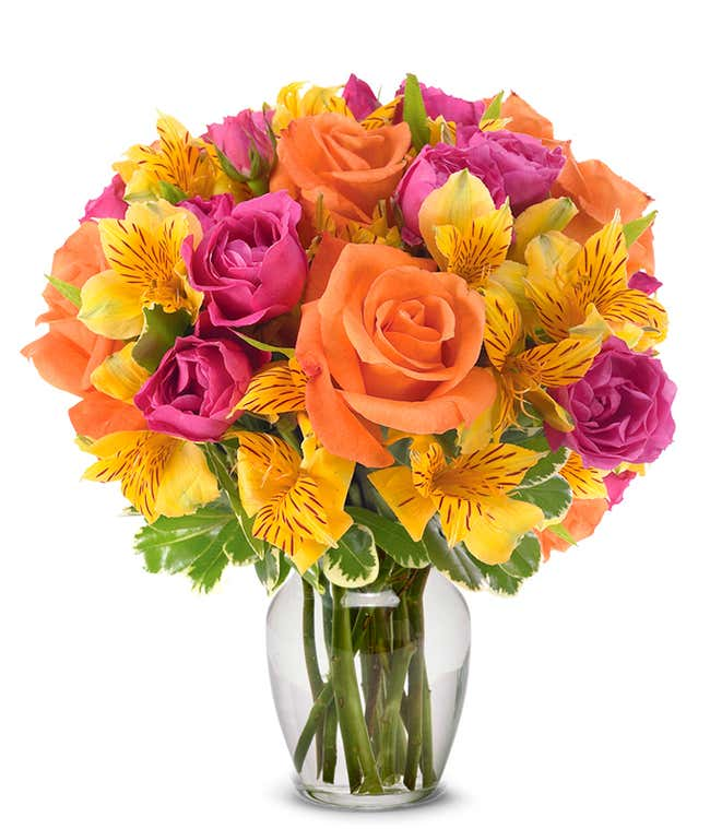 Orange roses, hot pink roses and yellow alstroemeria in glass vase