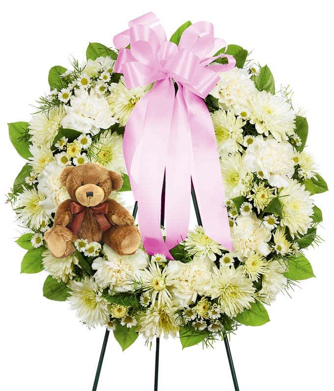 White floral funeral wreath with a pink bow and a teddy bear
