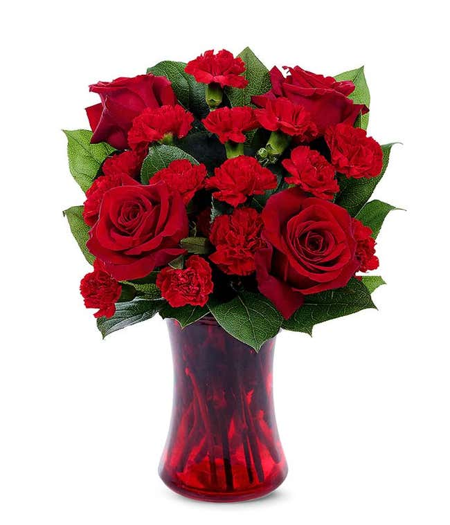 Red roses and red carnations in a red vase