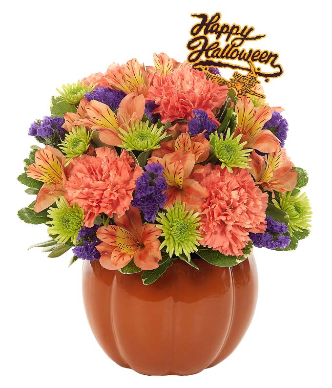 Orange, green and purple flowers in a pumpkin vase