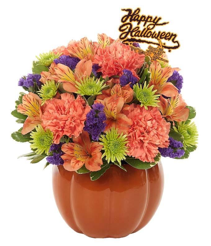 Orange, green and purple flowers in a pumpkin vase