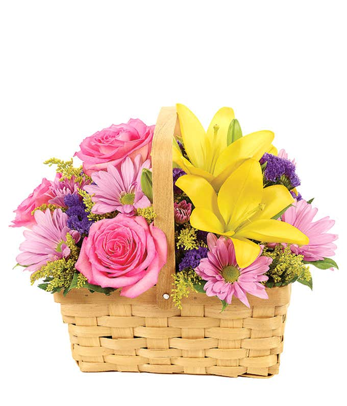 Yellow lilies, pink roses and purple daisies in a handled basket