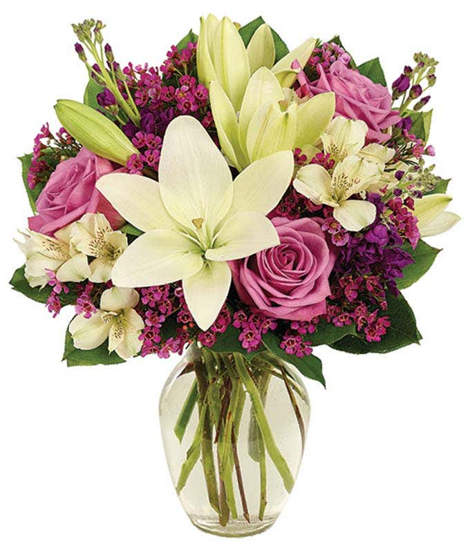 Purple roses and white lilies in a glass vase