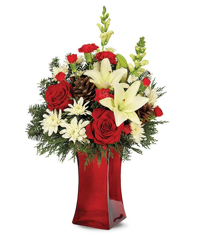 Red roses are arranged by a florist with white lilies, red carnations and pinecones in a tall red vase