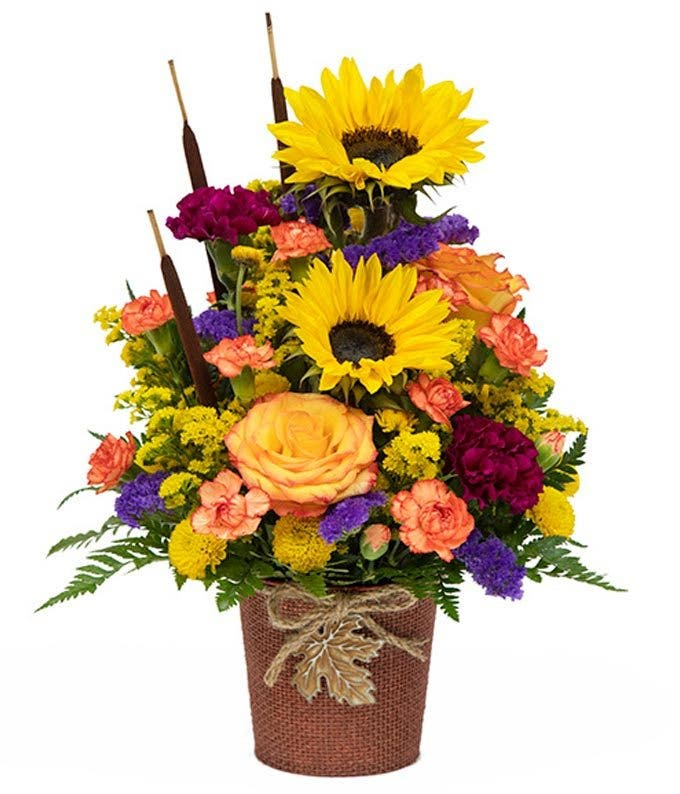 Mixed autumn with sunflowers, orange roses, orange carnations and maroon flowers.