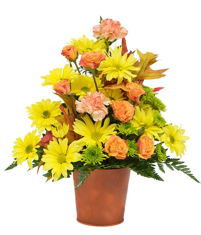 Yellow daisies with orange carnations in an orange pot
