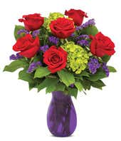 Red roses and green hydrangea in a purple vase