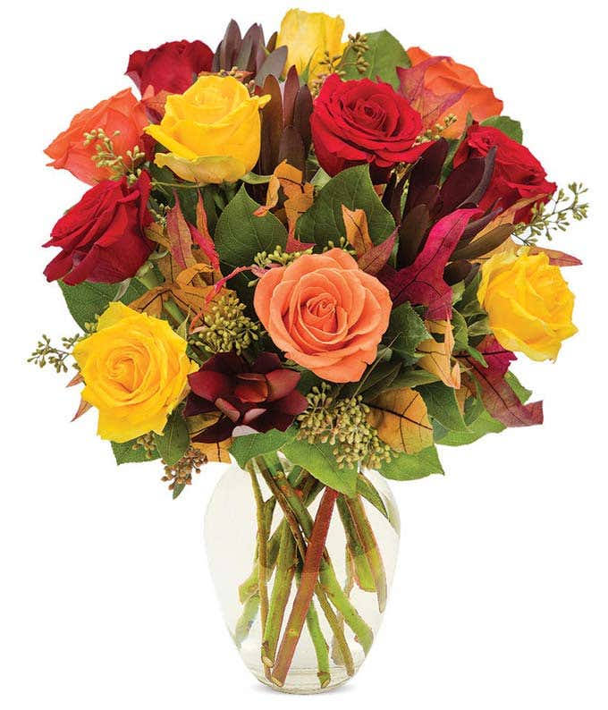Red roses, orange roses and yellow roses in a fall bouquet with fake leaves