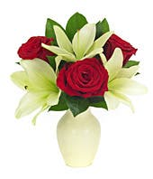 Red roses and white lilies in a white vase