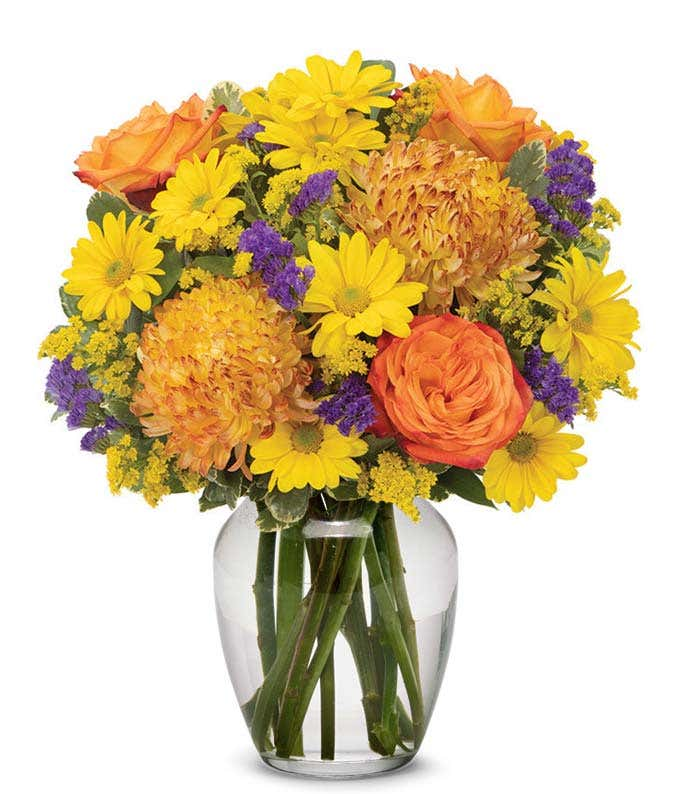 Bronze mums, Orange roses and yellow flowers in clear orange vase