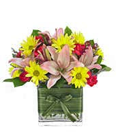 Pink lilies and yellow daisies in a modern vase
