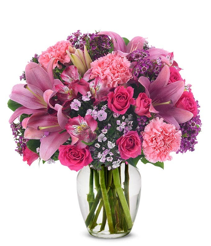 Pink carnations, pink spray roses and pink lilies in pink vase