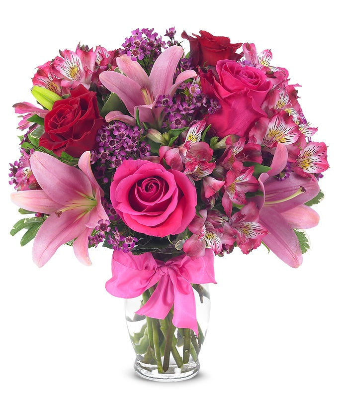 Red roses, pink lilies and pink alstroemeria and glass vase