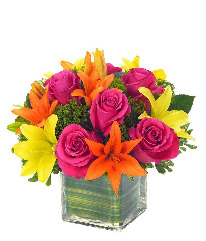 Orange and yellow Asiatic lilies and hot pink roses in square vase