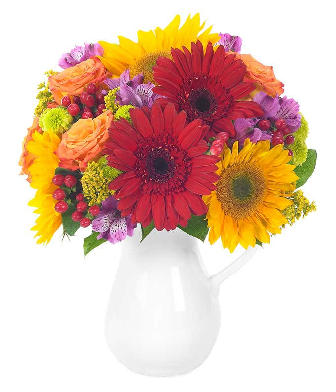 Red and yellow gerbera daisies, orange roses and hypericum in reusable pitcher