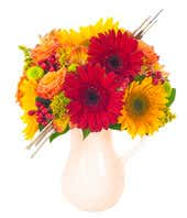 Orange roses, red gerbera daises and hypericum in pitcher for Fall