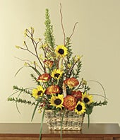 Orange roses and sunflowers in woven basket