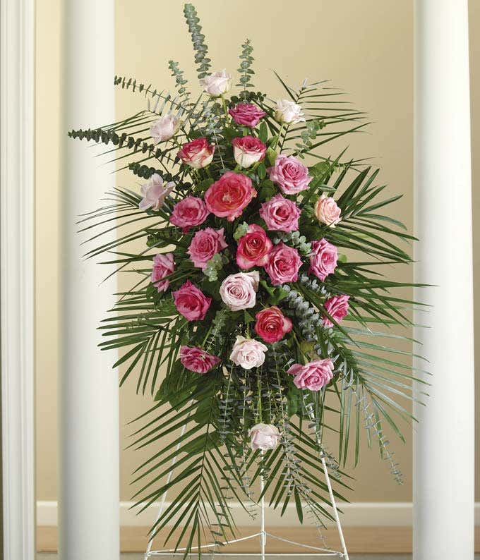 Mixed pink roses, spiral eucalyptus in a funeral standing spray