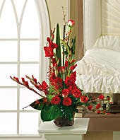 Sympathy arrangement of red gladiolus, roses and orchids