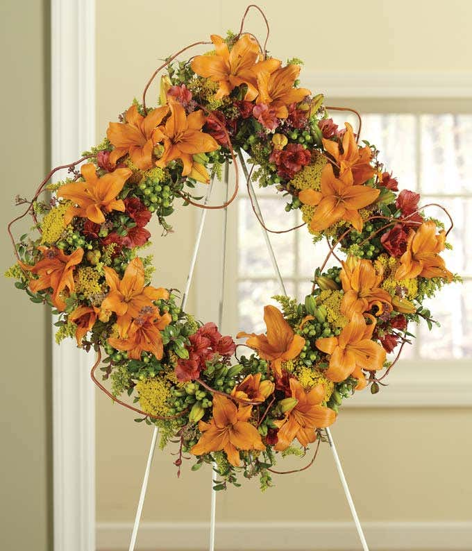 Orange lilies and red alstroemeria sympathy standing wreath