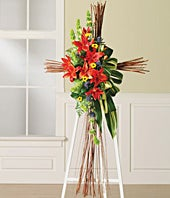 Red lilies and bells of Ireland in a funeral standing spray