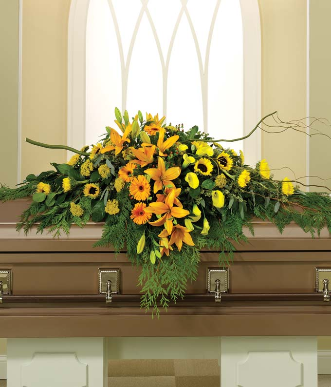 Sunflowers, orange lilies arranged into a casket spray