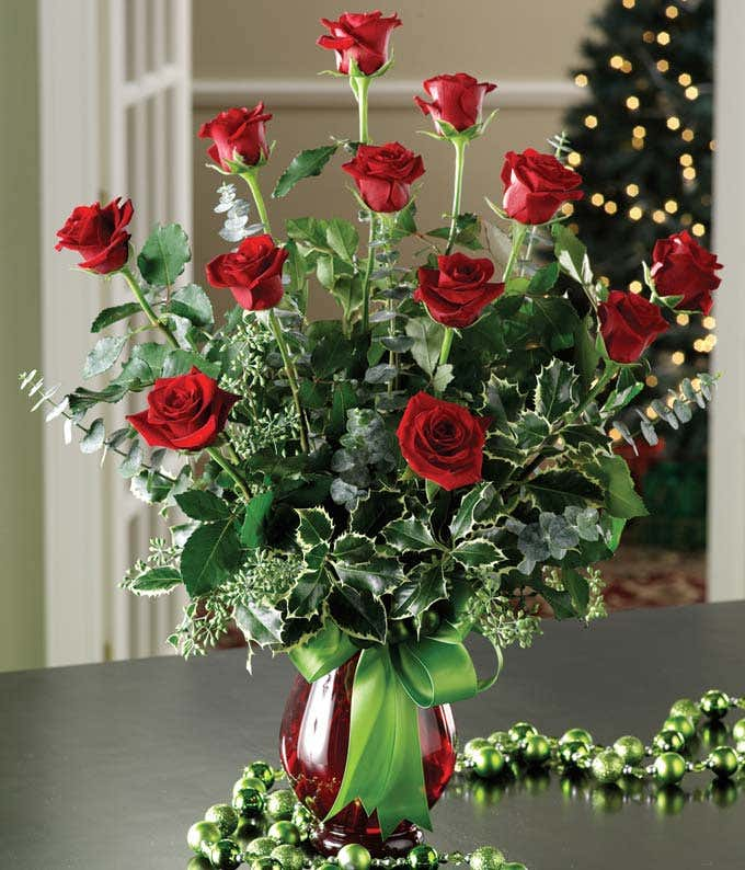 One dozen red roses with holly for Christmas