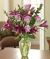 Purple roses and dark purple lilies in a glass vase