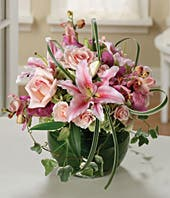 Pink roses, pink orchids and white lilies in a circular arrangement