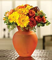 Orange, yellow and red gerbera daisies in a orange vase