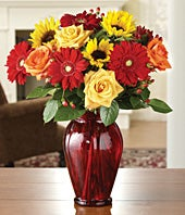 Yellow roses, orange roses, sunflowers and red gerbera daisies in red vase
