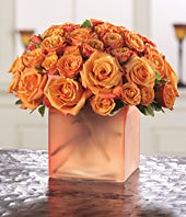 Orange roses and orange spray roses in colorful vase