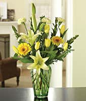 Yellow tulips, gerbera daisies and cream lilies in a bouquet