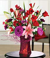 Purple carnations, pink lilies, pink roses and red rose bouquet