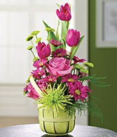 Pink tulips, purple roses and spider mums in basket for delivery