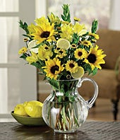 Send sunflowers and yellow roses in a pitcher