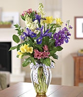 Purple irises, yellow and pink alstroemeria in glass vase