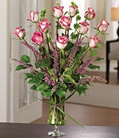 One dozen bi-color roses with seasonal greens in luxury vase