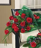 One dozen long stem red roses wrapped with a bow
