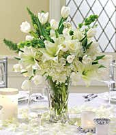 White lilies, tulips, roses and hydrangea in a centerpiece