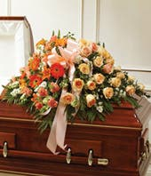 Orange roses and white snapdragon casket spray