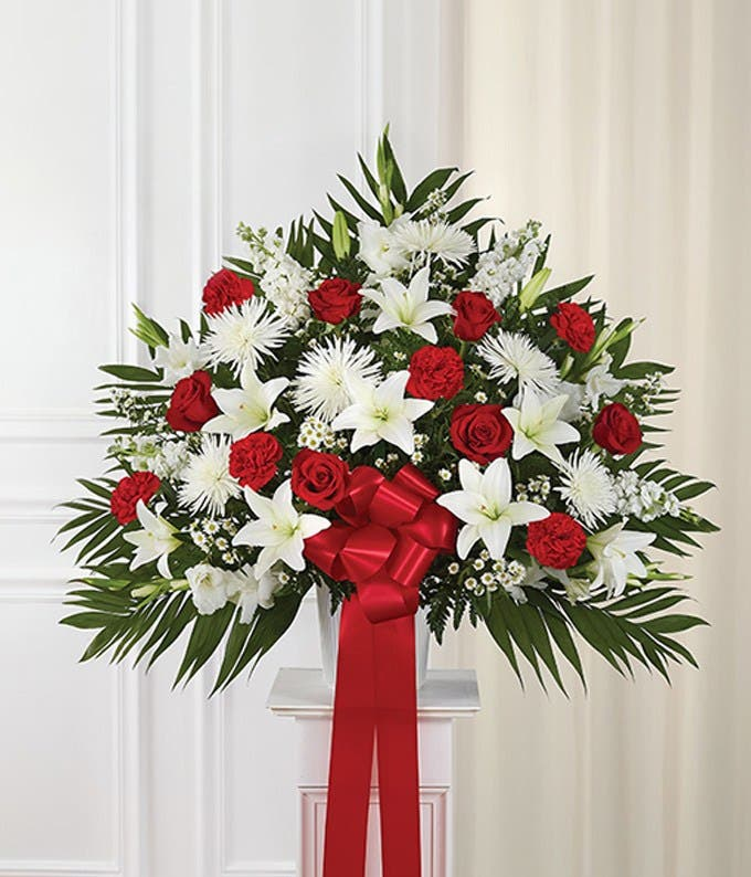 Sympathy flowers with red roses and white flowers in basket