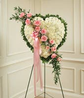 White flowers with pink rose break in heart shaped standing spray