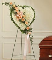 White carnations and peach rose break in funeral standing spray