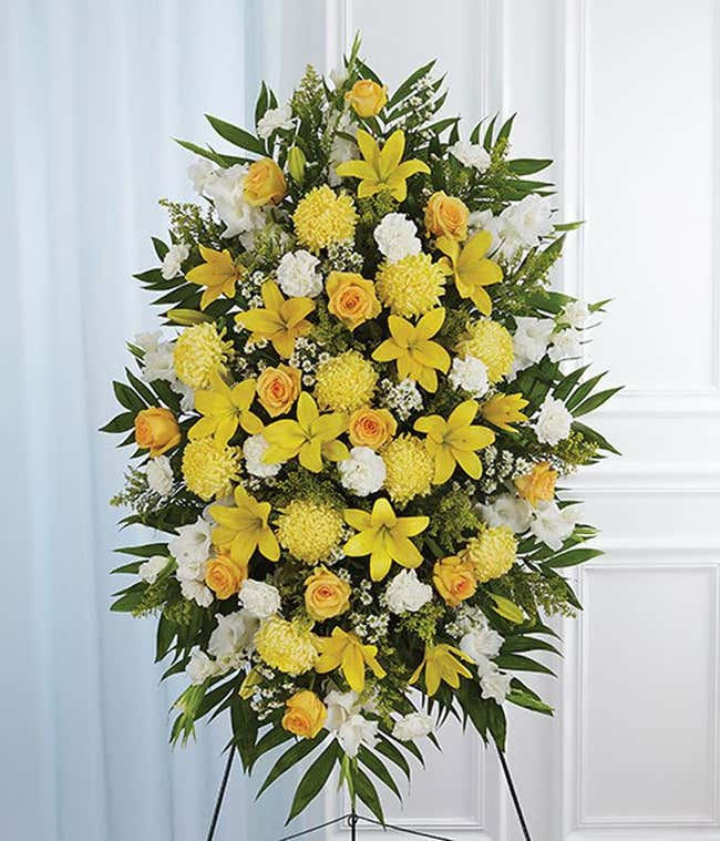 Yellow roses, yellow mums and white flowers in a standing spray