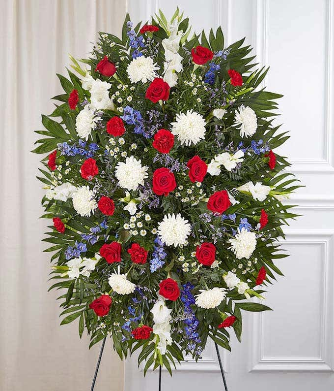 Sympathy spray with red flowers, and white flowers and blue flowers