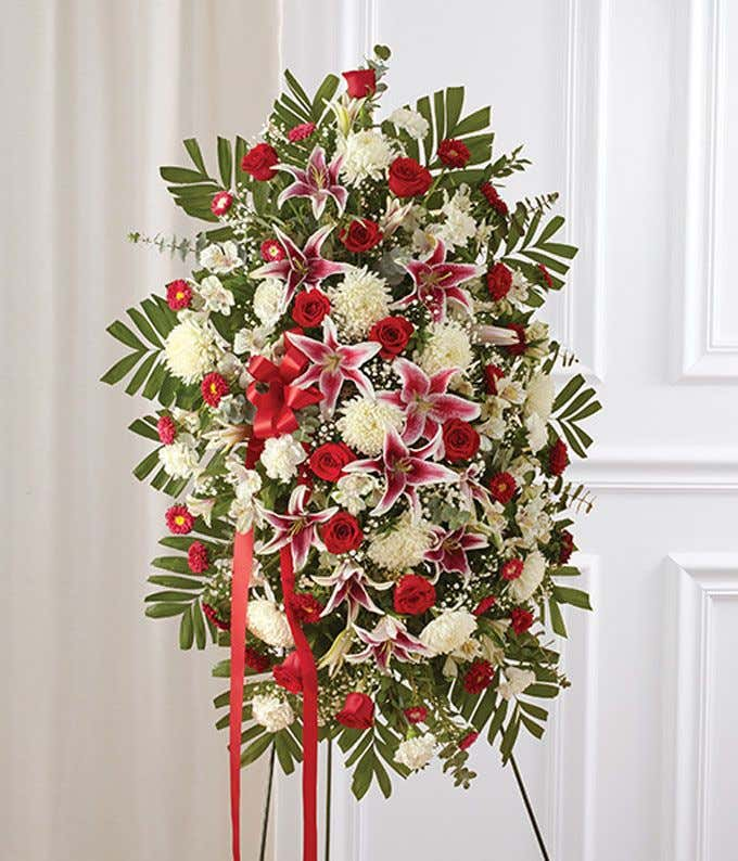 Red roses, gerbera daisies and spray roses in a standing spray