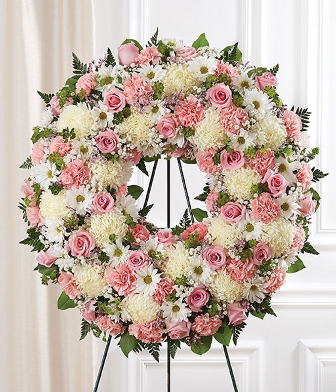 Pink roses, white daisies, and white mums in a funeral wreath